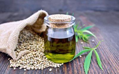 a jar of hemp oil with a sack of hemp seeds at the back