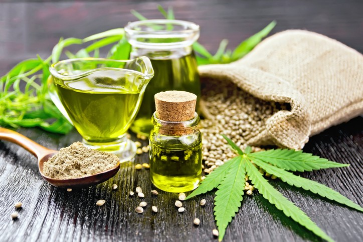 hemp seeds and leaves with a bottle of hemp oil